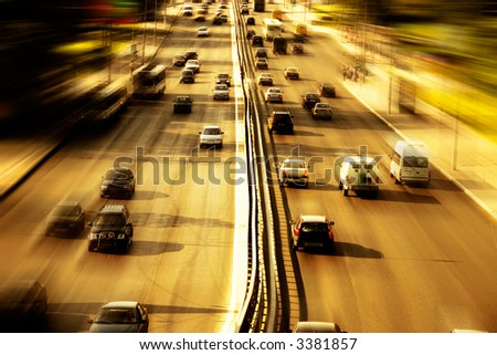 Highway with lots of cars. Red sunset light, high contrast and motion blur to rise speed. - stock photo