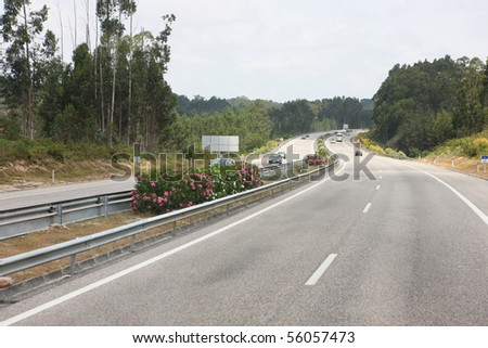 highway with several cars in both ways - stock photo