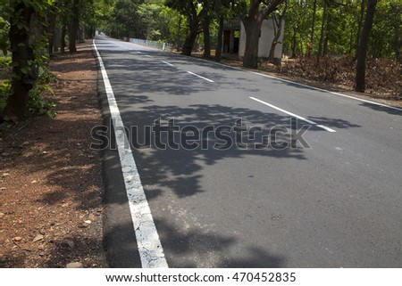 Highway with shadow of trees on road