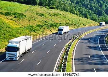 Highway with three oncoming white truck in a wooded landscape, slope with meadow and forest, view from above - stock photo