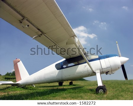 Highwing monoplane parked on grass field - stock photo