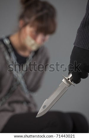 hijacker with knife and helpless female hostage - stock photo