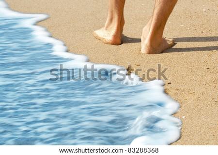 hike along the beach with bare feet - stock photo