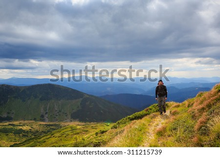 Hike journey lonely man on the mountain trails. Dramatic cloudy sky. Alone with the beautiful nature. Back to basics. Series of photos - stock photo