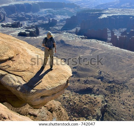 Hiker admires the vista from a risky perch - stock photo