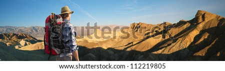 Hiker admiring the sunrise at Zabriskie point, Death valley, standing with his back to the camera, with a backpack and walking sticks on his back - stock photo
