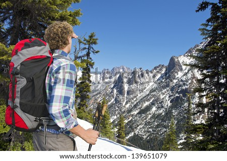 Hiker admiring the view on the snowy mountains of the Kangaroo ridge from the Washington Pass overlook in the North Cascades Range, with the melting snow on a warm spring day - stock photo