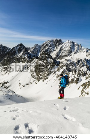 Hiker against Tatra ridge in winter conditions.