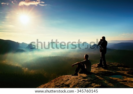 Hiker and photo enthusiast stay with tripod on cliff and thinking. Dreamy fogy landscape, blue misty sunrise in a beautiful valley below, soft focus - stock photo