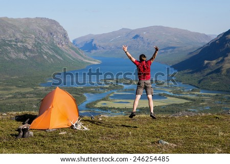 Hiker and Tent over Rautasjaure in Sweden - stock photo