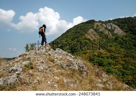 Hiker arrives at the top of the mountain - stock photo