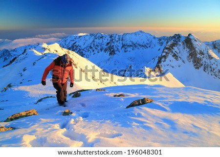 Hiker ascending the snow covered summit at sunset - stock photo