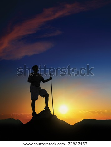 Hiker at the summit of a mountain with the sun rising in the background