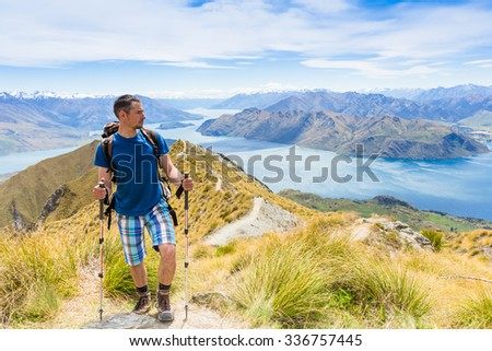 hiker at the top his hands raised enjoy sunny day. New Zealand - stock photo