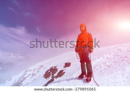 hiker at the top of a pass with backpacks meeting the sunrise in the mountains