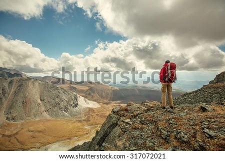 hiker at the top of a rock with backpack enjoy sunny day - stock photo