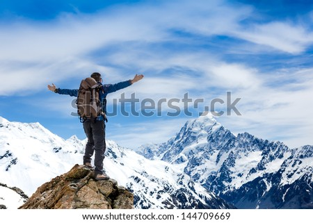 hiker at the top of a rock with his hands raised enjoy sunny day