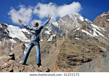 hiker at the top of a rock with snowy mountains on the horizon - stock photo