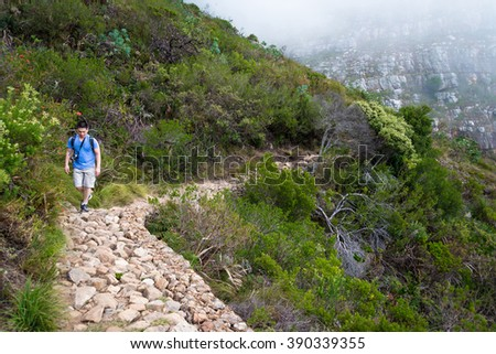Hiker climbing Table Mountain via Platteklip Gorge, taking a rest.  Table Mountain is a new Seven Wonder of the Natural World located in Cape Town, South Africa. - stock photo