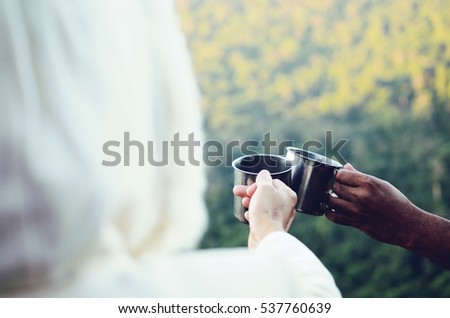 Hiker couple drinking coffee in the mountains.close up hands