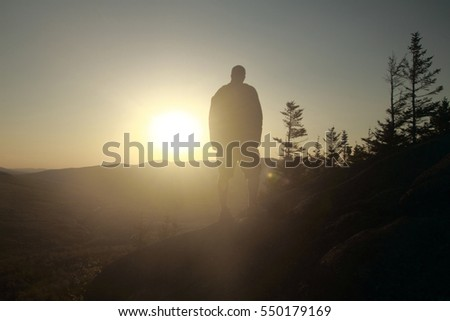Hiker enjoying the mountain views from the summit of Pine Mountain in Gorham, New Hampshire USA at sunset.