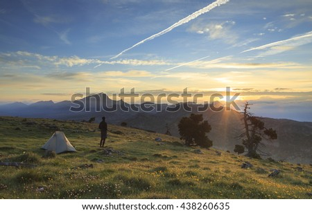 Hiker enjoying the summer sunrise at his tent while camping in the mountains.