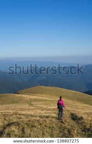 Hiker enjoying the view and going downhill in the mountains - stock photo