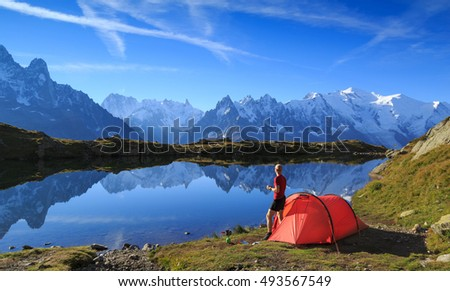 Hiker enjoying the view over Lac De Cheserys from his red tent in the mountains near Chamonix, France.