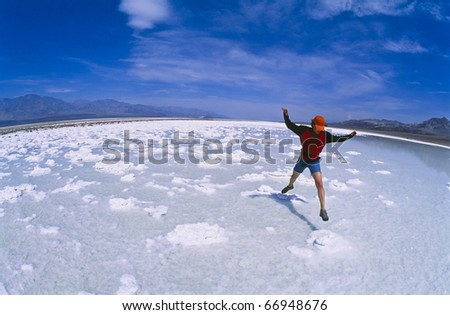 Hiker explores and jumps across salt deposits in the Devils Golfcourse, Death Valley National Park. - stock photo