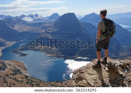 Hiker gazing at mountain lake - stock photo