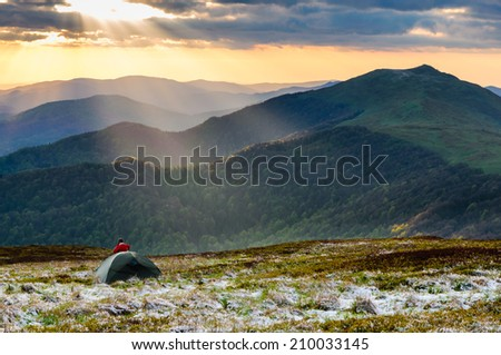 Hiker gets out of her tent on the ridge of Bieszczady mountains to watch amazing sunset - stock photo