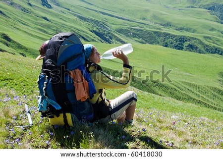 Hiker girl drinking water after hard rush and relaxing on the meadow.