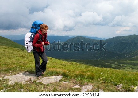 Hiker girl going by track in mountains