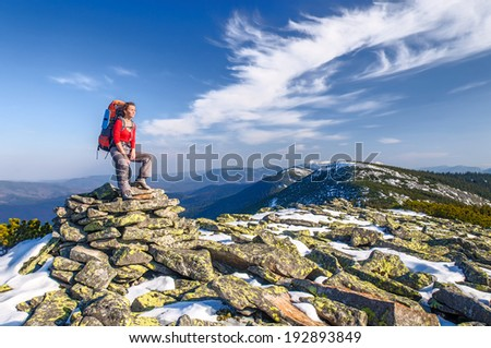 Hiker girl with backpack  in a mountains - stock photo