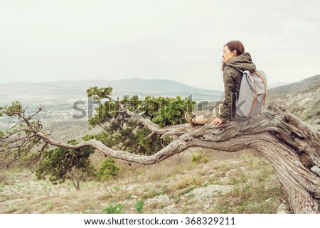 Hiker girl with backpack sitting on juniper tree and enjoying view of nature in the mountains