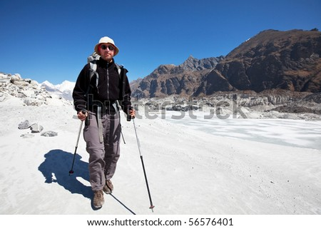 Hiker going along glacier  in Himalayan mountain - stock photo