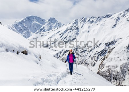 Hiker happy woman trekking on the snowy Caucasus mountains at spring - stock photo