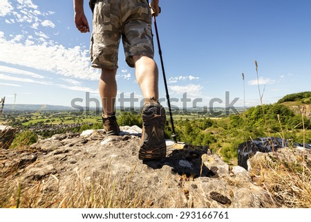 Hiker hiking on a mountain trail with distant views of countryside in summer sunshine - stock photo