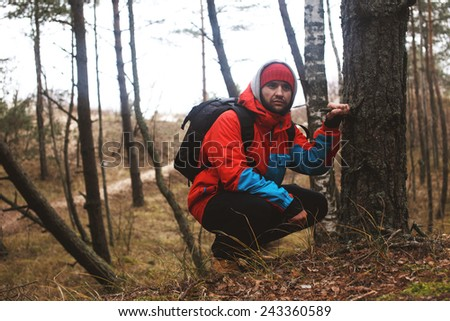 Hiker hunkered down near a tree have a rest time  - stock photo