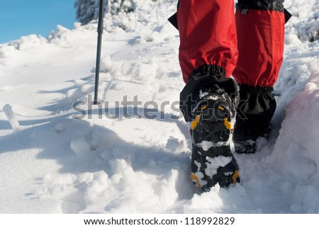 hiker in a winter mountain, trekking boots close-up