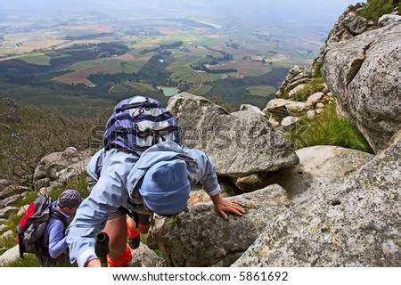 Hiker in blue climbs on steep mountain - and misty majestic landscape as background. Shot in the Helderberg Mountains nature reserve, Western Cape, South Africa. - stock photo