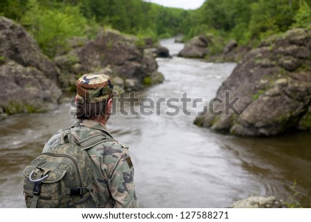 Hiker in camouflage clothing on the rocky shore of a mountain river. Russia. Primorskiy kray. - stock photo