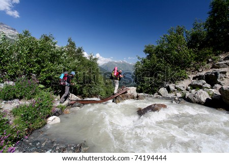 Hiker in Caucasus mountains is crossing mountain river - stock photo
