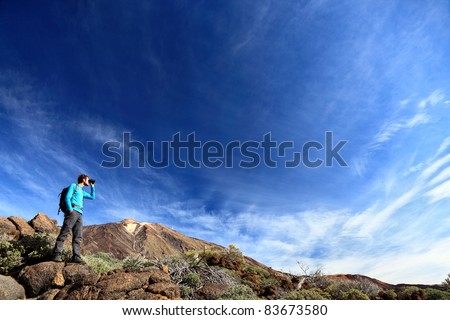 hiker in dramatic landscape hiking under deep blue sky looking in binoculars. Young Caucasian man during hike in Mountain landscape on volcano Teide, Tenerife, Canary Islands - stock photo