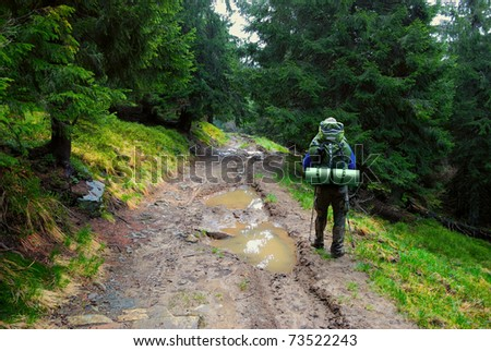 hiker in forest and puddle on dirt road