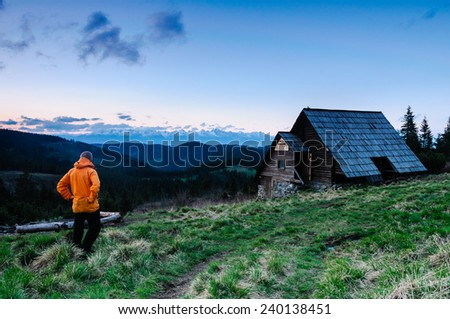 Hiker in front of beautiful mountain hut with looking at sharp peaks of High Tatras in the background in the evening - stock photo