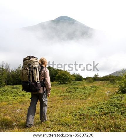 hiker in mountains on green glade - stock photo