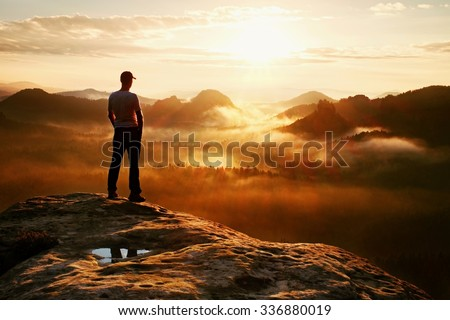 Hiker in red cap stand on the peak of sandstone rock in rock empires park and watching over the misty and foggy morning valley to Sun. Beautiful moment the miracle of nature
