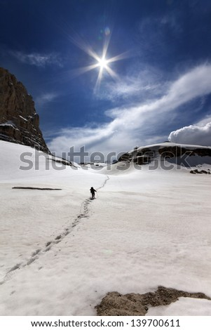 Hiker in snowy mountains. Turkey, Central Taurus Mountains, Aladaglar (Anti-Taurus), plateau Edigel (Yedi Goller) - stock photo