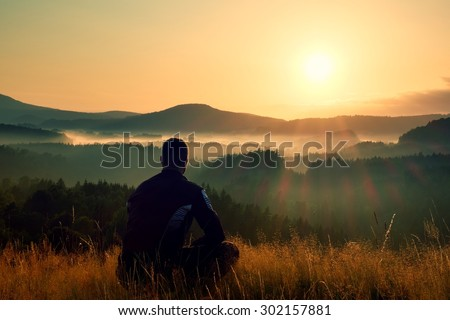 Hiker in squatting position in high grass meadow  enjoy the colorful sunrise scenery - stock photo
